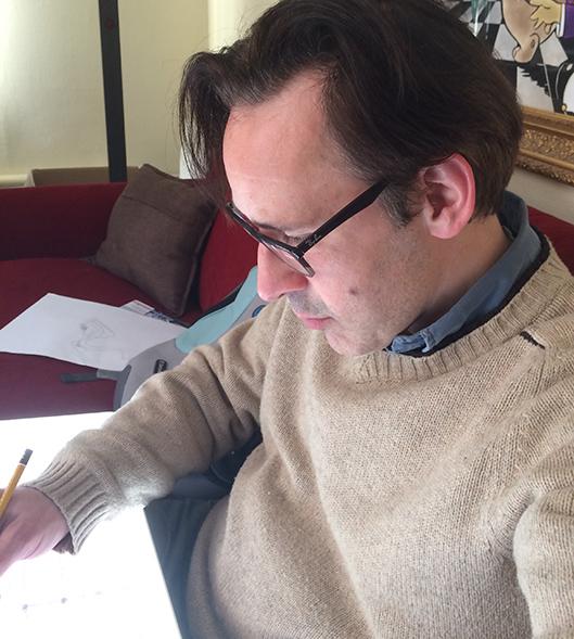 Stefan de Groot trekt de schetsen over op aquarel papier op een lichttafel.